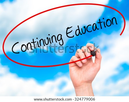 Man Hand writing Continuing Education with black marker on visual screen. Isolated on sky. Business, technology, internet concept. Stock Photo - stock photo