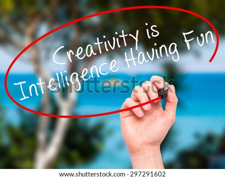Man Hand writing Creativity is Intelligence Having Fun with black marker on visual screen. Isolated on nature. Business, technology, internet concept. Stock Photo - stock photo