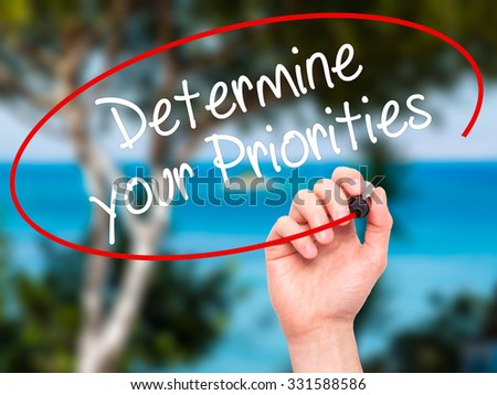 Man Hand writing Determine your Priorities with black marker on visual screen. Isolated on nature. Business, technology, internet concept. Stock Photo - stock photo