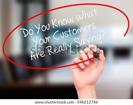 Man Hand writing Do You Know What Your Customers Are Really Saying? with black marker on visual screen. Isolated on background. Business, technology, internet concept. Stock Photo