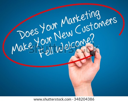Man Hand writing Does Your Marketing Make Your New Customers Fell Welcome?  with black marker on visual screen. Isolated on white. Business, technology, internet concept. Stock Photo