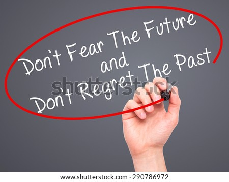 Man Hand writing Don't Fear The Future and Don't Regret The Past with black marker on visual screen. Isolated on grey. Life, technology, internet concept. Stock Image