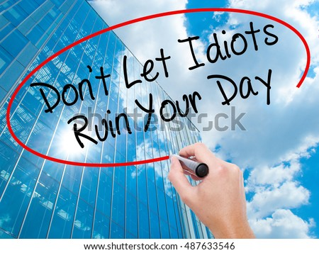Man Hand writing Don't Let Idiots Ruin Your Day with black marker on visual screen. Business, technology, internet concept. Modern business skyscrapers background. Stock Photo