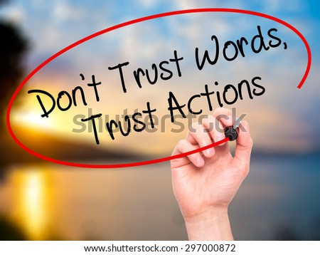 Man Hand writing Don't Trust Words, Trust Actions with black marker on visual screen. Isolated on nature. Business, technology, internet concept. Stock Photo - stock photo