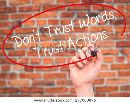 Man Hand writing Don't Trust Words, Trust Actions with black marker on visual screen. Isolated on bricks. Business, technology, internet concept. Stock Photo - stock photo