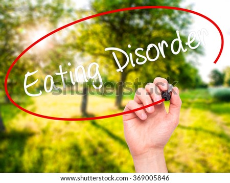 Man Hand writing Eating Disorder  with black marker on visual screen. Isolated on background. Business, technology, internet concept. Stock Photo - stock photo