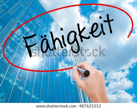 Man Hand writing Fahigkeit (Ability in German) with black marker on visual screen.  Business, technology, internet concept. Modern business skyscrapers background. Stock Photo