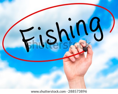 Man Hand writing Fishing with black marker on visual screen. Isolated on sky. Business, technology, internet concept. Stock Image