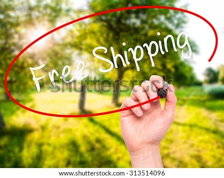 Man Hand writing Free Shipping with black marker on visual screen. Isolated on nature. Business, technology, internet concept. Stock Photo - stock photo