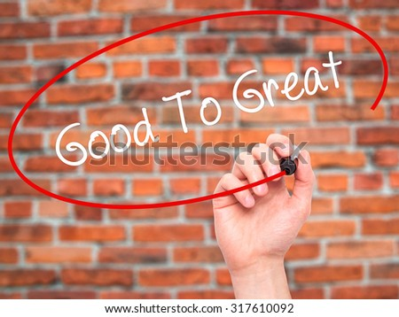 Man Hand writing Good To Great with black marker on visual screen. Isolated on bricks. Business, technology, internet concept. - stock photo