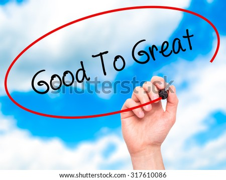 Man Hand writing Good To Great with black marker on visual screen. Isolated on sky. Business, technology, internet concept. - stock photo