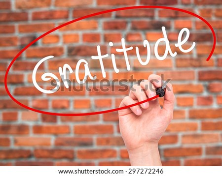 Man Hand writing Gratitude with black marker on visual screen. Isolated on bricks. Business, technology, internet concept. Stock Photo - stock photo
