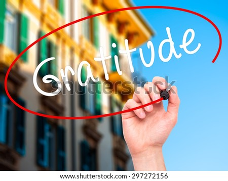 Man Hand writing Gratitude with black marker on visual screen. Isolated on city. Business, technology, internet concept. Stock Photo - stock photo