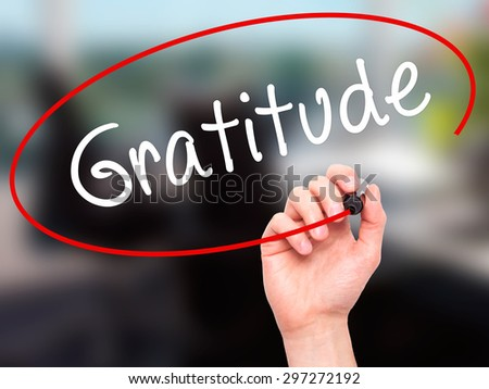 Man Hand writing Gratitude with black marker on visual screen. Isolated on office. Business, technology, internet concept. Stock Photo - stock photo
