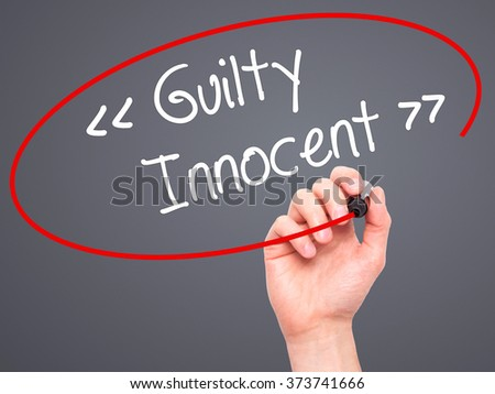Man Hand writing Guilty - Innocent with black marker on visual screen. Isolated on background. Business, technology, internet concept. Stock Photo - stock photo