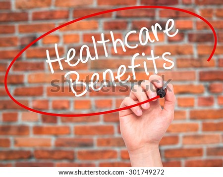 Man Hand writing Healthcare Benefits with black marker on visual screen. Isolated on bricks. Business, technology, internet concept. Stock Photo - stock photo