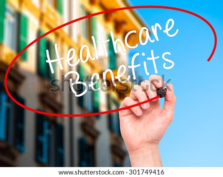 Man Hand writing Healthcare Benefits with black marker on visual screen. Isolated on city. Business, technology, internet concept. Stock Photo - stock photo