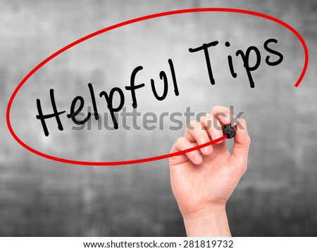 Man hand writing Helpful Tips on visual screen. Business,help, internet, technology concept. Isolated on grey. Stock Photo - stock photo