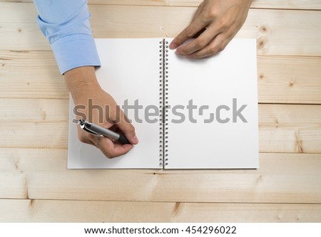 Man hand writing his idea on book .Top view