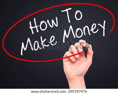 Man Hand writing How To Make Money with black marker on visual screen. Isolated on black. Business, technology, internet concept. Stock Image - stock photo