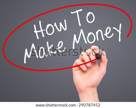 Man Hand writing How To Make Money with black marker on visual screen. Isolated on grey. Business, technology, internet concept. Stock Image - stock photo