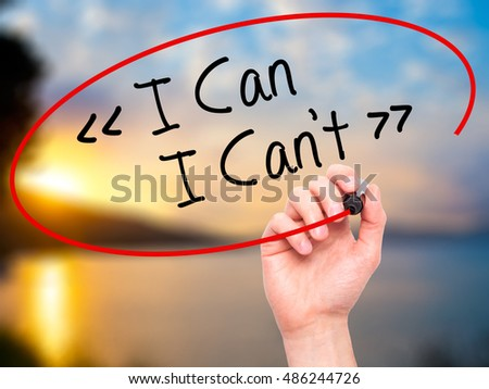 Man Hand writing I Can - I Can't with black marker on visual screen. Isolated on background. Business, technology, internet concept. Stock Photo