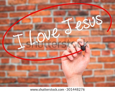 Man Hand writing I Love Jesus with black marker on visual screen. Isolated on bricks. Business, technology, internet concept. Stock Photo - stock photo