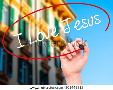 Man Hand writing I Love Jesus with black marker on visual screen. Isolated on city. Business, technology, internet concept. Stock Photo - stock photo