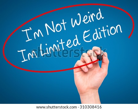 Man Hand writing I'm Not Weird Im Limited Edition with black marker on visual screen. Isolated on blue. Business, technology, internet concept. Stock Photo - stock photo