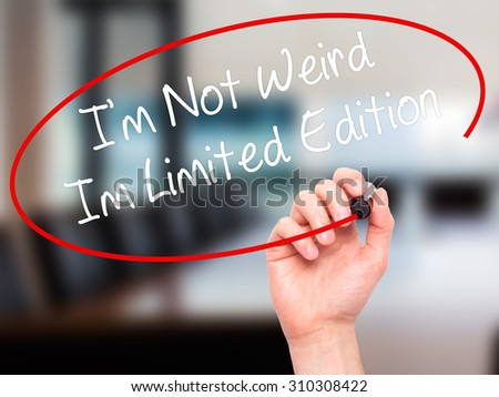 Man Hand writing I'm Not Weird Im Limited Edition with black marker on visual screen. Isolated on office. Business, technology, internet concept. Stock Photo - stock photo