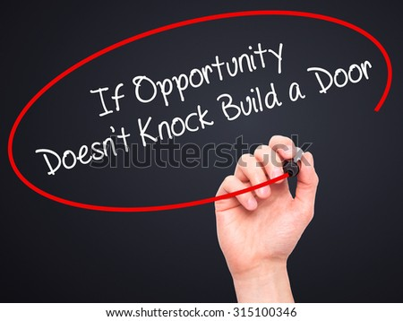 Man Hand writing If Opportunity Doesn't Knock Build a Door with black marker on visual screen. Isolated on black. Business, technology, internet concept. Stock Photo - stock photo