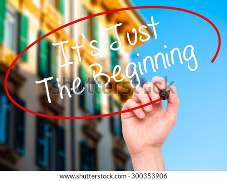 Man Hand writing It's Just The Beginning with black marker on visual screen. Isolated on city. Business, technology, internet concept. Stock Photo - stock photo