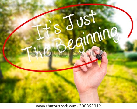 Man Hand writing It's Just The Beginning with black marker on visual screen. Isolated on nature. Business, technology, internet concept. Stock Photo - stock photo