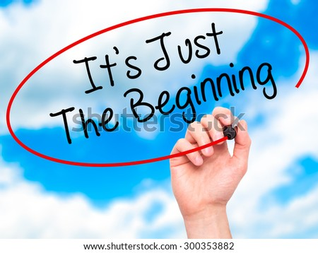 Man Hand writing It's Just The Beginning with black marker on visual screen. Isolated on sky. Business, technology, internet concept. Stock Photo - stock photo