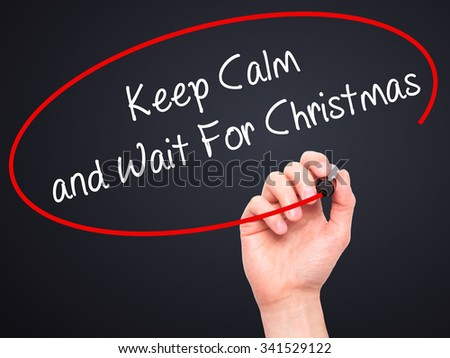 Man Hand writing Keep Calm and Wait For Christmas with black marker on visual screen. Isolated on black. Business, technology, internet concept. Stock Photo