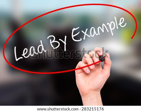 Man Hand writing Lead By Example with marker on transparent wipe board. Isolated on office. Business, internet, technology concept. Stock Photo - stock photo
