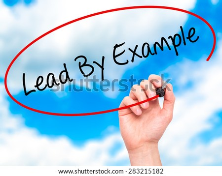 Man Hand writing Lead By Example with marker on transparent wipe board. Isolated on sky. Business, internet, technology concept. Stock Photo - stock photo