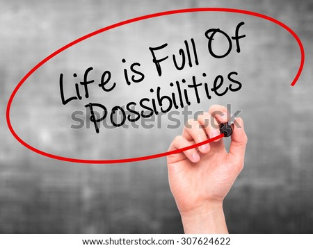 Man Hand writing Life is Full Of Possibilities with black marker on visual screen. Isolated on grey. Business, technology, internet concept. Stock Photo