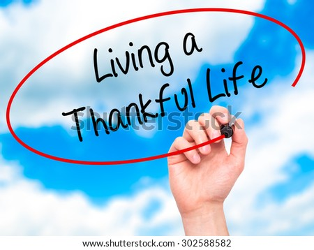 Man Hand writing Living a Thankful Life with black marker on visual screen. Isolated on sky. Business, technology, internet concept.  - stock photo