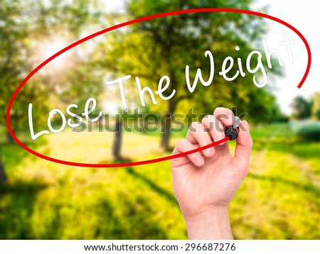 Man Hand writing Lose The Weight with black marker on visual screen. Isolated on nature. Business, technology, internet concept. Stock Photo - stock photo