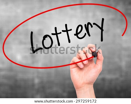 Man Hand writing Lottery  with black marker on visual screen. Isolated on grey. Business, technology, internet concept. Stock Photo - stock photo