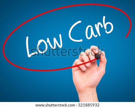 Man Hand writing Low Carb with black marker on visual screen. Isolated on blue. Business, technology, internet concept. - stock photo