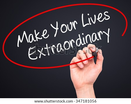 Man Hand writing Make Your Lives Extraordinary with black marker on visual screen. Isolated on background. Business, technology, internet concept. Stock Photo