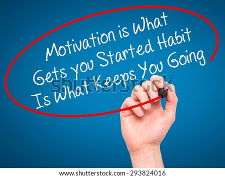 Man Hand writing Motivation is What Gets you Started Habit Is What Keeps You Going with black marker on visual screen. Isolated on blue. Business, technology, internet concept. Stock Photo - stock photo