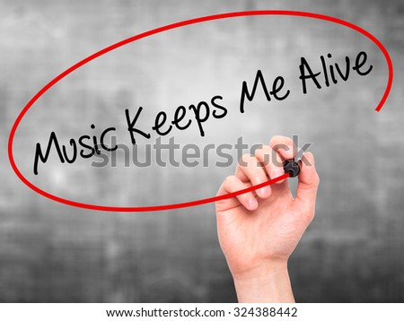 Man Hand writing Music Keeps Me Alive with black marker on visual screen. Isolated on grey. Business, technology, internet concept. Stock Photo - stock photo