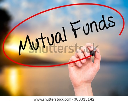 Man Hand writing Mutual Funds  with black marker on visual screen. Isolated on nature. Business, technology, internet concept. Stock Photo - stock photo