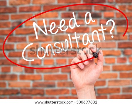 Man Hand writing Need a Consultant? with black marker on visual screen. Isolated on bricks. Business, technology, internet concept. Stock Photo - stock photo
