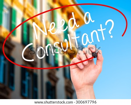 Man Hand writing Need a Consultant? with black marker on visual screen. Isolated on city. Business, technology, internet concept. Stock Photo - stock photo