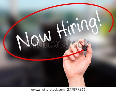 Man Hand writing Now Hiring! with marker on transparent wipe board. Isolated on office. Business, internet, technology concept.  Stock Photo - stock photo