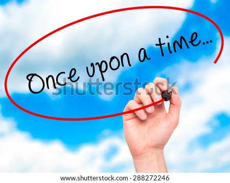 Man Hand writing Once upon a time... with black marker on visual screen. Isolated on sky. Business, technology, internet concept. Stock Image - stock photo
